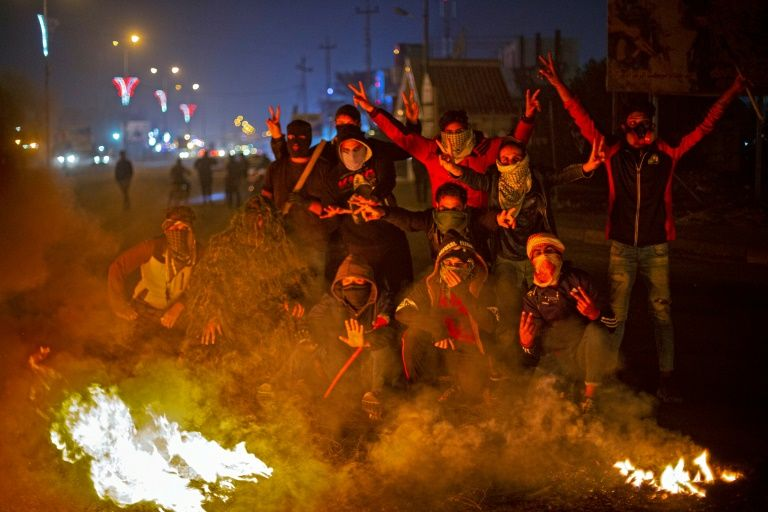 Iraqi anti-government protesters at a makeshift roadblock in the southern city of Basra (AFP Photo/Hussein FALEH)